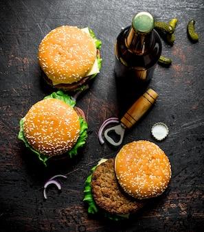Hambúrgueres com cerveja em uma garrafa na mesa rústica escura.