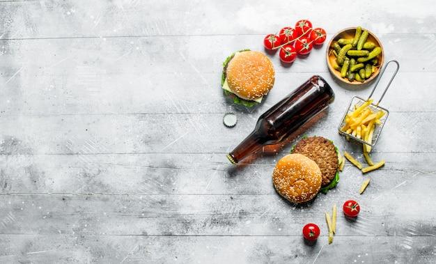 Hambúrgueres com cerveja na garrafa, pepinos e batatas fritas em mesa rústica