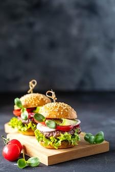 Hambúrgueres com costeleta de carne, alface fresca, tomate, cebola em uma pedra escura. copie o espaço