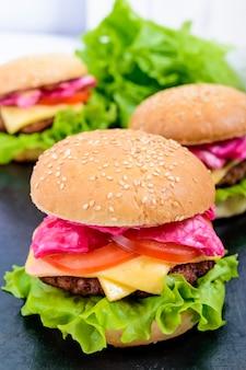Hambúrgueres com costeleta suculenta, tomate, repolho e pepino em conserva, queijo, folhas verdes de alface e um pão macio com gergelim