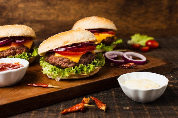Hambúrgueres com ketchup na bandeja de madeira