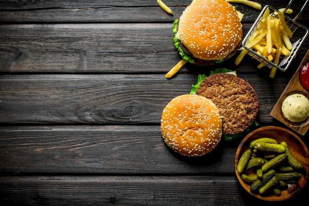 Hambúrgueres com pepinos em tigela, batatas fritas e molhos. em fundo preto de madeira