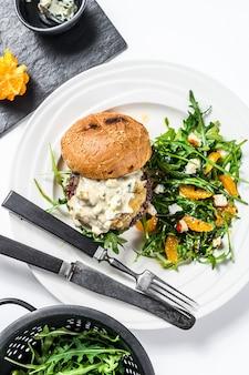 Hambúrgueres com queijo azul, marmelada de carne e cebola, um prato de salada com rúcula e laranjas. fundo branco. vista do topo