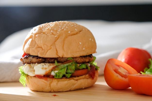 Hambúrgueres com queijo, saladas e legumes em uma placa de madeira de espaço em branco.
