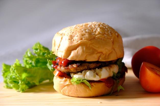 Hambúrgueres com queijo, saladas e vegetais em espaço em branco