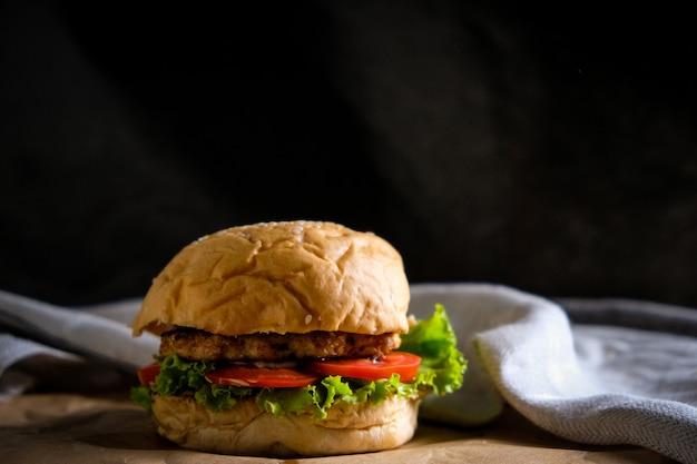 Hambúrgueres com queijo, saladas e vegetais em espaço negro