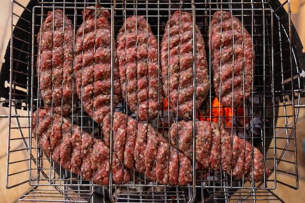 Hambúrgueres cozinhando na grelha, copie o espaço.