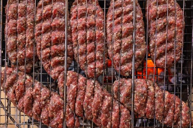 Hambúrgueres cozinhando na grelha, copie o espaço. Foto Premium