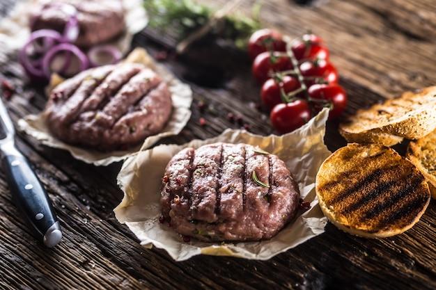 Hambúrgueres crus na mesa de madeira com ervas, tomate cebola e especiarias.