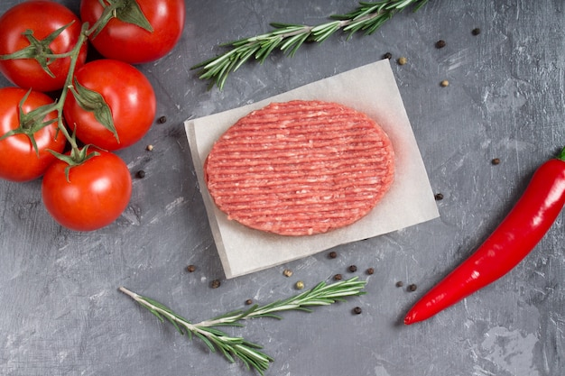Hamburgueres crus no papel de pergaminho com tomates, pimentas e alecrins.
