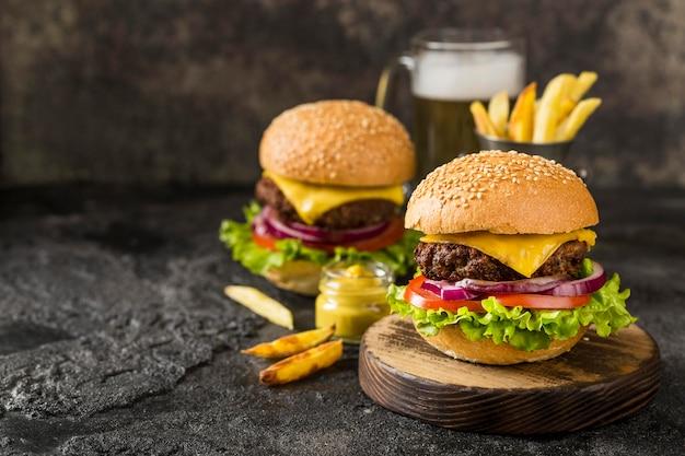 Hambúrgueres de alto ângulo com batata frita, molho e cerveja com cópia-espaço