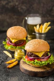 Hambúrgueres de alto ângulo com batata frita, molho e cerveja