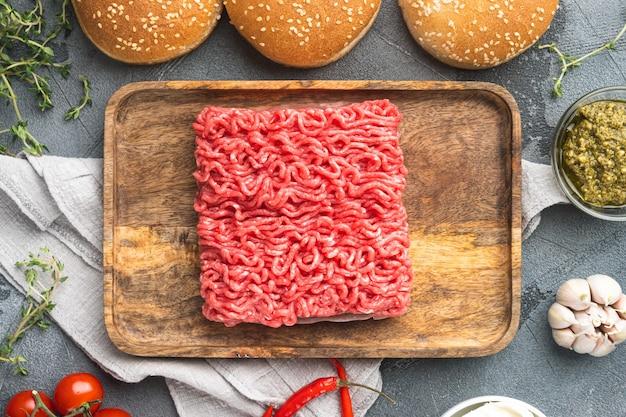 Hambúrgueres de bife de carne crua fresca com ingredientes de especiarias colocados em uma bandeja de madeira sobre pedra cinza