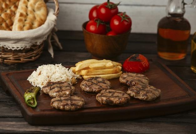Hambúrgueres de carne de bovino servidos com batata frita, arroz e legumes grelhados