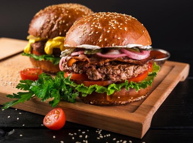 Hambúrgueres de carne deliciosa em uma placa de madeira