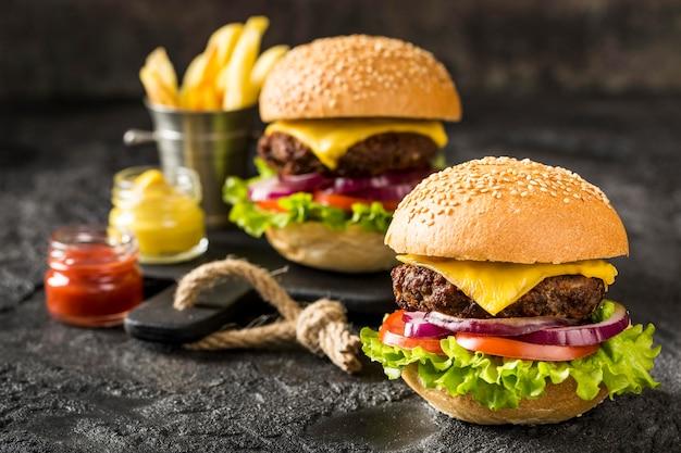 Hambúrgueres de carne na tábua de cortar com batatas fritas e molho