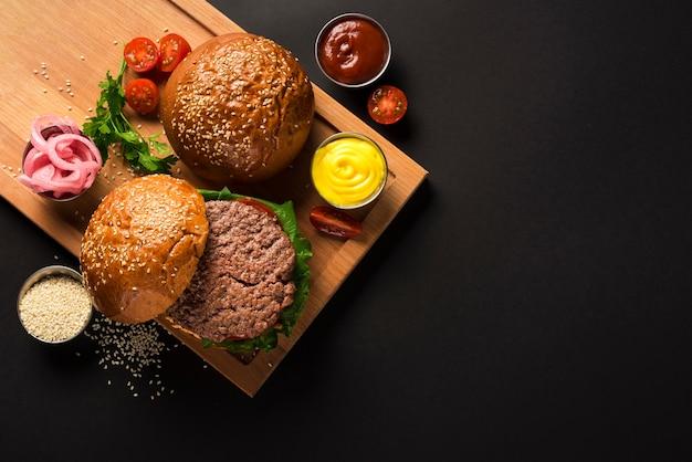 Hambúrgueres de carne saborosa em uma placa de madeira com molhos