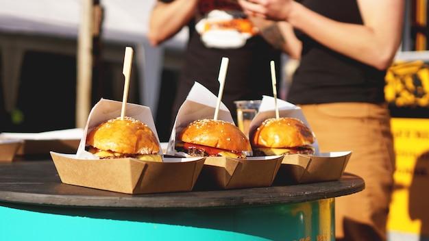 Hambúrgueres de carne servidos em barraca de comida em cozinha aberta, evento do festival internacional de comida de comida de rua