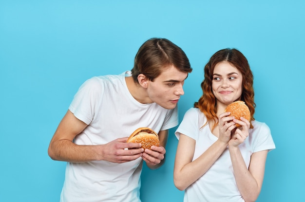 Hambúrgueres de casal jovem nas mãos, lanche, estilo de vida, fundo azul