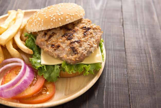 Hambúrgueres de churrasco com batatas fritas na mesa de madeira.