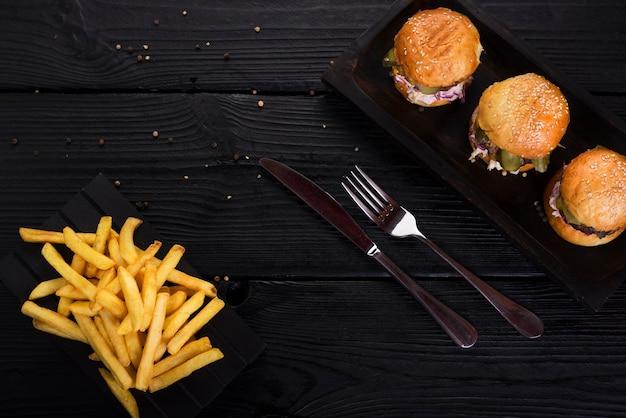 Hambúrgueres de fast-food com batatas fritas e talheres