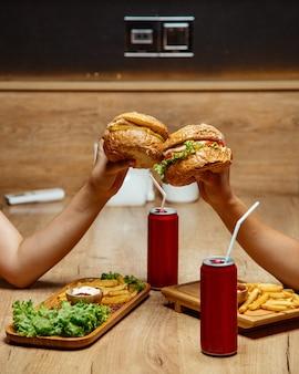 Hambúrgueres de frango coca-cola e batatas fritas em uma placa de madeira