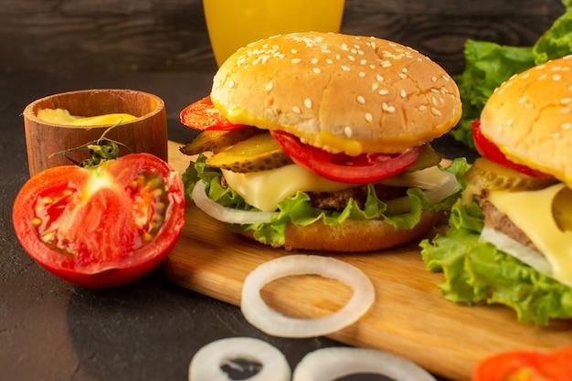 Hambúrgueres de frango com queijo e salada verde acompanhados de suco na mesa de madeira e sanduíches fast-food