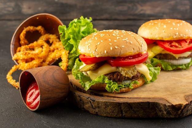 Hambúrgueres de frango com queijo e salada verde na mesa de madeira e sanduíches fast-food