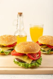 Hambúrgueres de frango com queijo, salada verde, suco e azeite de oliva na mesa de madeira e sanduíches fast-food