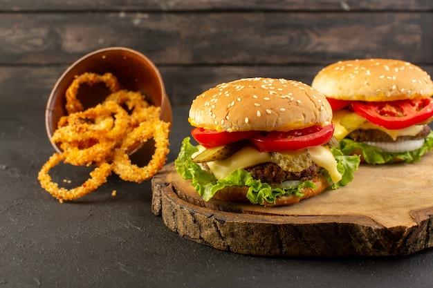 Hambúrgueres de frango com salada de queijo verde e anéis de cebola na mesa de madeira e sanduíches fast-food