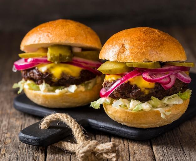 Hambúrgueres de frente com pickles e cebolas vermelhas na tábua