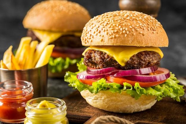 Hambúrgueres de frente na tábua com batatas fritas e molhos