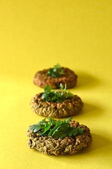 Hambúrgueres de lentilha close up vertical, fundo amarelo com espaço de cópia