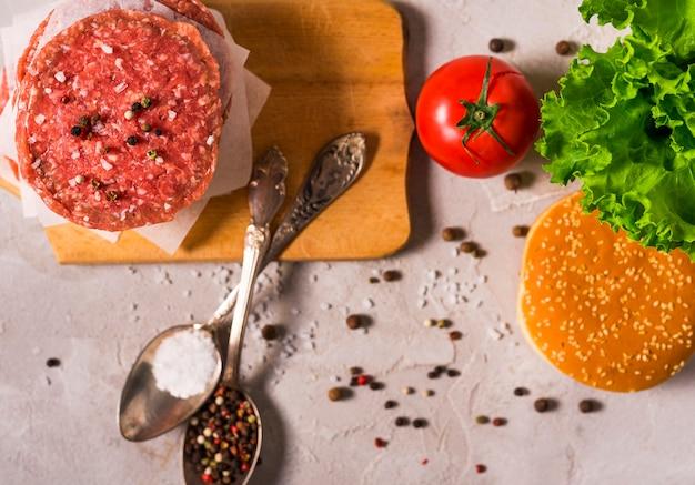 Hambúrgueres de patty de vista superior com tomate e colheres