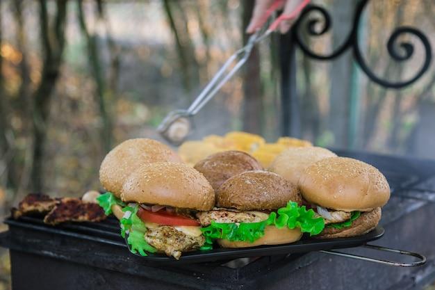 Hambúrgueres de peito com legumes na grelha a carvão quente com a mão no fundo