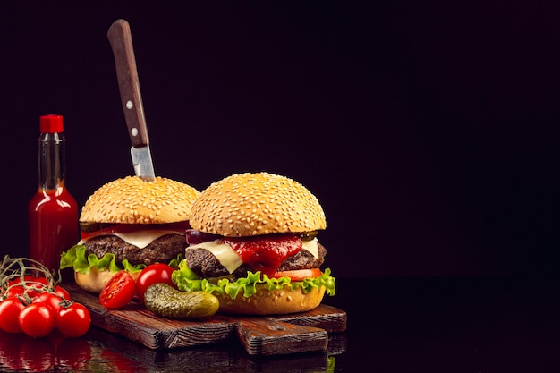 Hambúrgueres de vista frontal com fundo preto