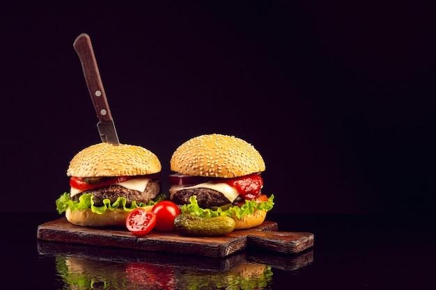 Hambúrgueres de vista frontal em uma placa de corte
