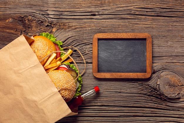 Hambúrgueres de vista superior em um saco com lousa