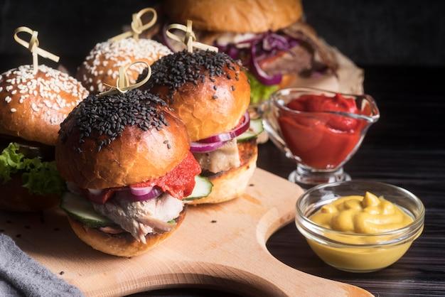 Hambúrgueres deliciosos na placa de madeira