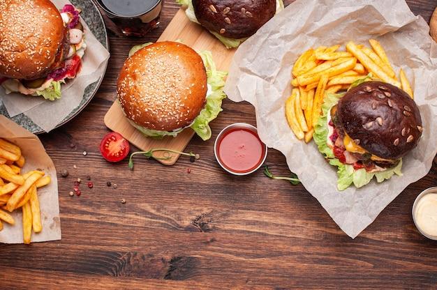Hambúrgueres e batatas fritas no tampo de madeira