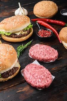 Hambúrgueres e os ingredientes frescos na superfície de madeira escura.