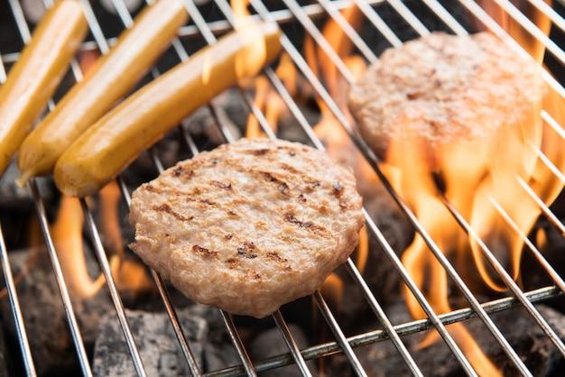 Hambúrgueres e salsichas, cozinhando em chamas na grelha.