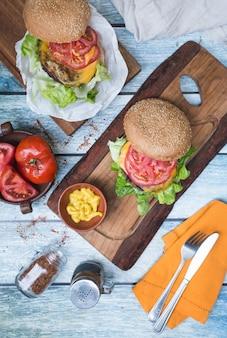 Hambúrgueres em uma mesa, mostarda e tomate