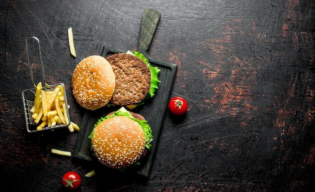 Hambúrgueres em uma tábua preta e batatas fritas em mesa rústica