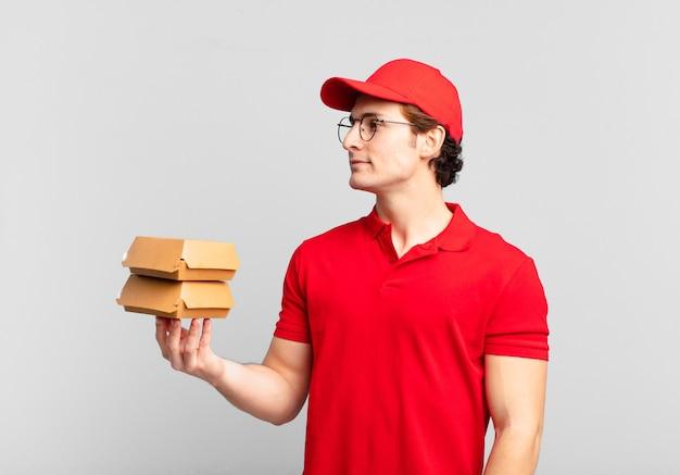 Hambúrgueres entregam menino em vista de perfil olhando para copiar o espaço à frente, pensando, imaginando ou sonhando acordado