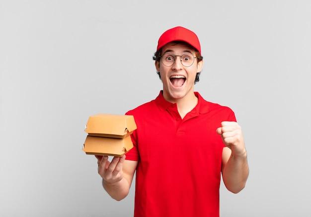 Hambúrgueres entregam menino sentindo-se chocado, animado e feliz, rindo e comemorando o sucesso, dizendo uau!