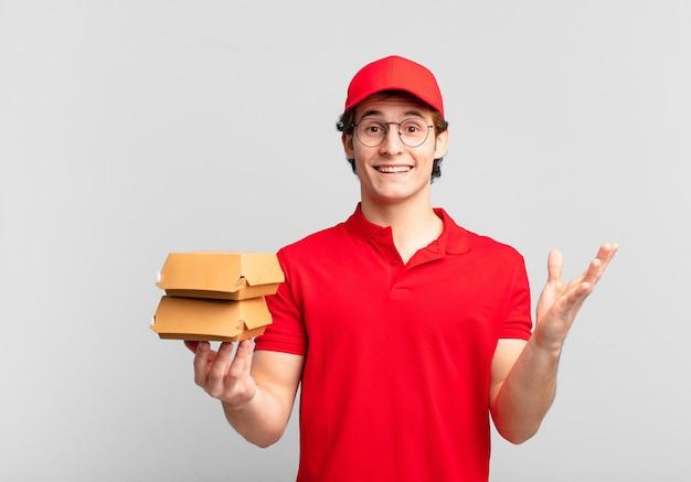 Hambúrgueres entregam menino sentindo-se feliz, surpreso e alegre, sorrindo com atitude positiva, percebendo uma solução ou ideia
