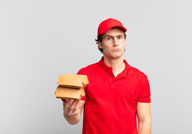 Hambúrgueres entregam menino sentindo-se triste, chateado ou com raiva e olhando para o lado com uma atitude negativa, franzindo a testa em desacordo
