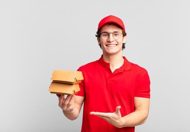 Hambúrgueres entregam menino sorrindo alegremente, se sentindo feliz e mostrando um conceito no espaço da cópia com a palma da mão