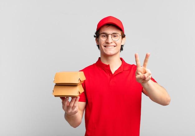 Hambúrgueres entregam menino sorrindo e parecendo feliz, despreocupado e positivo, gesticulando vitória ou paz com uma mão